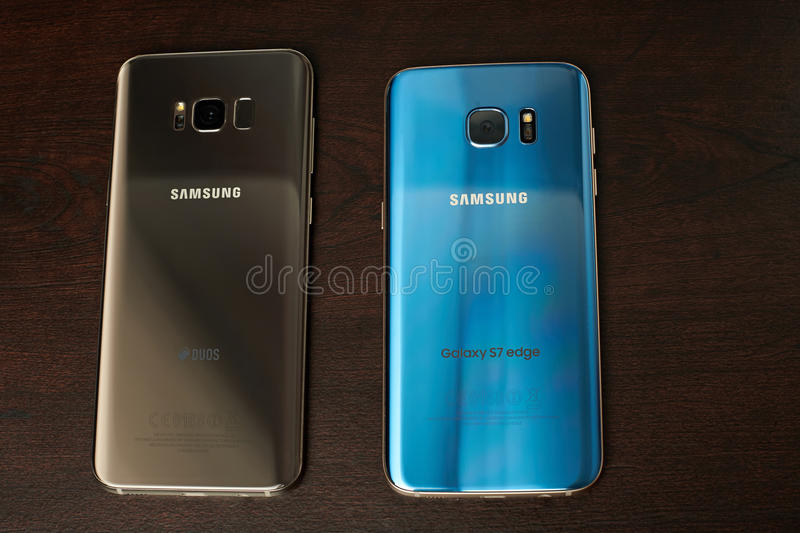 Gold and blue Samsung s8 plus and s7 edge smartphone. New york, USA - June 13, 2017: Gold and blue Samsung s8 plus and s7 edge smartphone on dark wooden surface royalty free stock photo