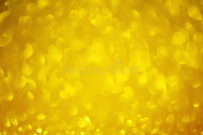 Gold bokeh hearts Background with Bright glitter Lights for Valentine`s Day or Women day, 8 march. Defocused shine golden texture royalty free stock photos