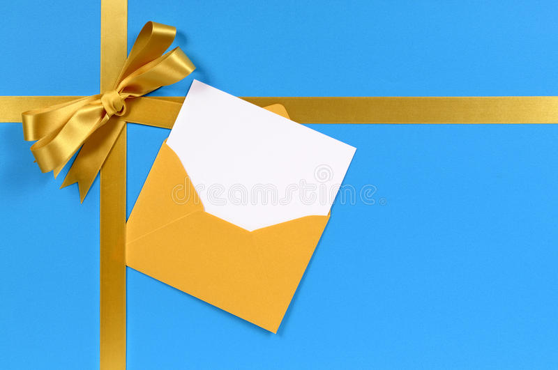 Gold bow, gift ribbon, christmas card in envelope, blue background. Blue and gold gift with blank invitation or greetings card stock photo