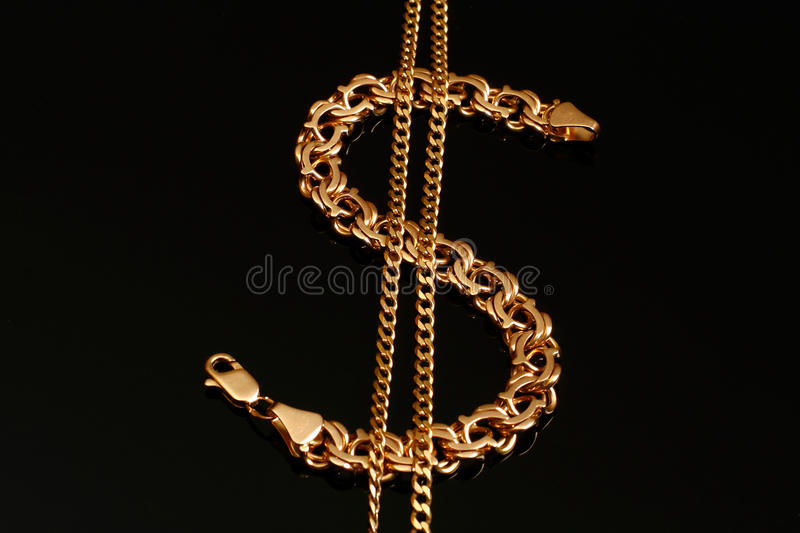 A gold bracelet and a chain. In the form of dollar signs stock photo