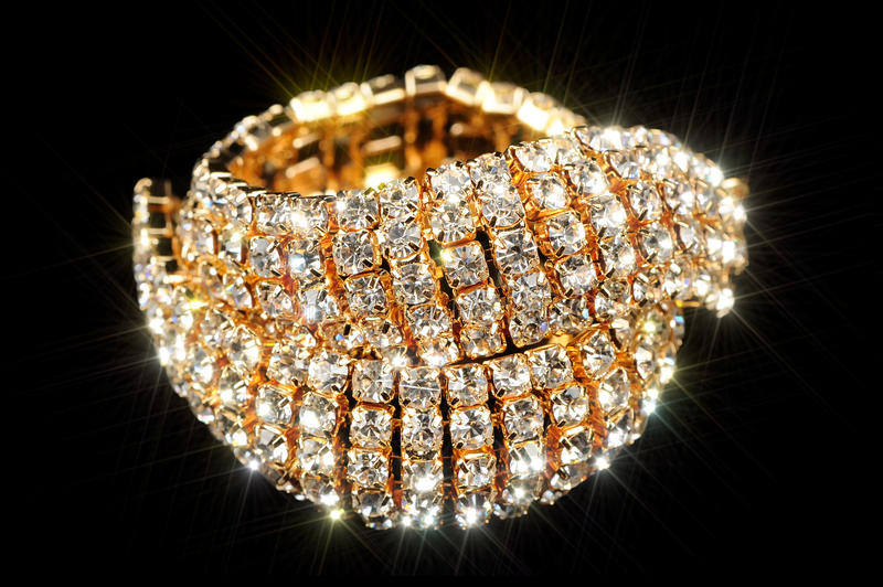 Gold Bracelet with Cubic Zirconia (CZ) on Black Background. A beautiful shiny gold bracelet with cubic zirconia (diamond substitute) against a black background stock image