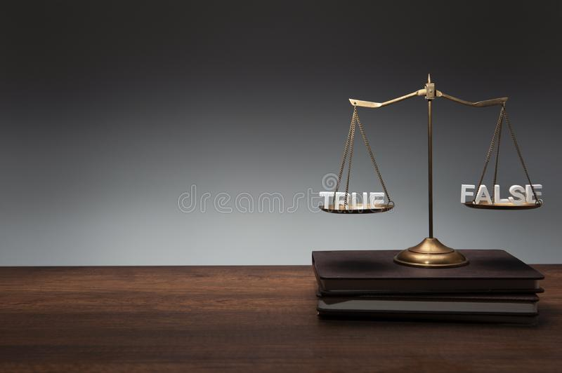 Gold brass balance scale place on notebooks and wooden desk and gray backdrop with wood text TRUE FALSE. On the scale, law and justice concept royalty free stock photos