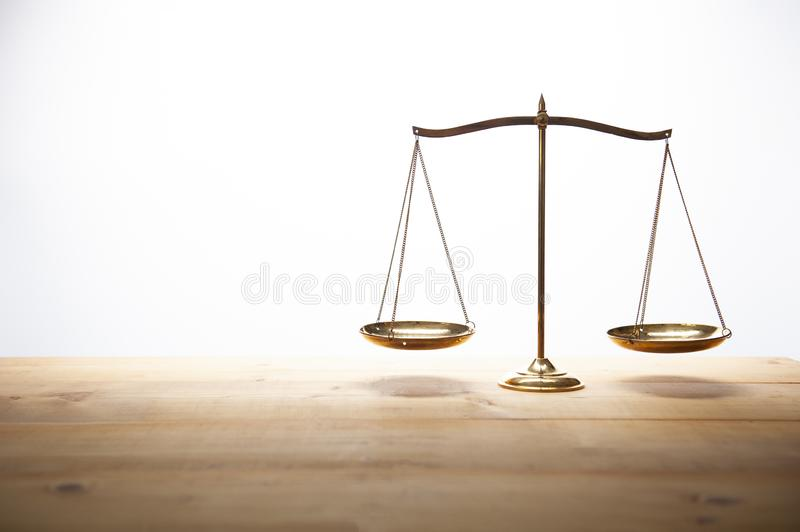 Gold brass balance scale on wooden desk and white backdrop. Law and justice concept stock image