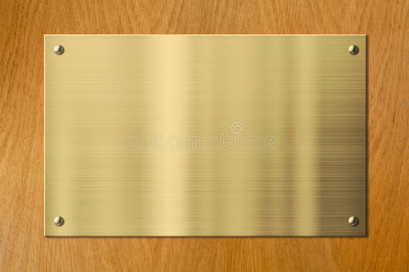 Gold or brass metal plaque on wood background stock image for Plaque de metal adhesive