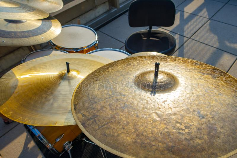 Gold bronze drum symbols drum set with empty chair with setting. Band on brake leaving an un maned drum set outside royalty free stock photography