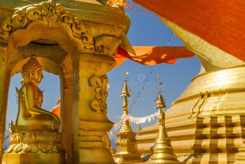 Gold-Buddha-Statue in der goldenen Pause vor Gold-stupa mit den orange buddhistischen wellenartig bewegenden und fliegenden Flagg lizenzfreie stockbilder