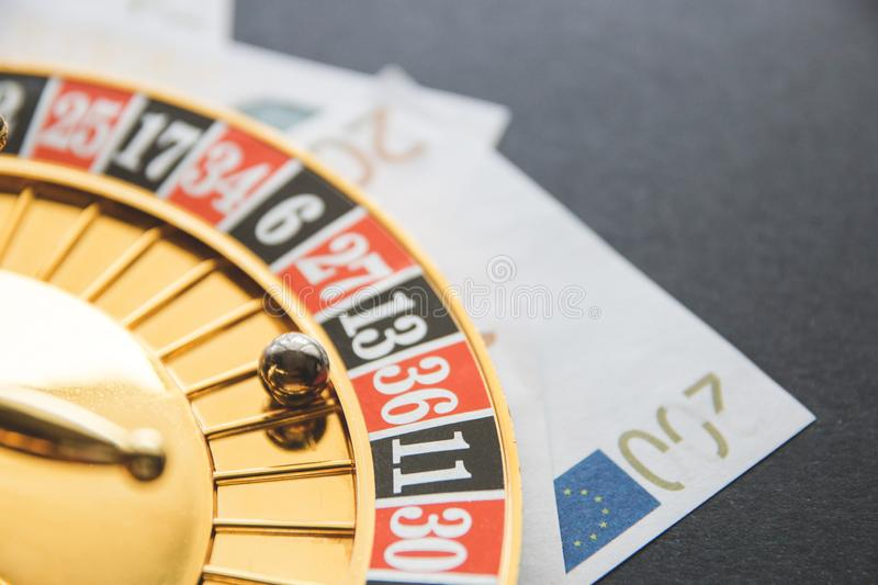 Gold casino theme. Image of casino roulette, poker games, money on the table, all on a dark bokeh background. Place for printing royalty free stock photography