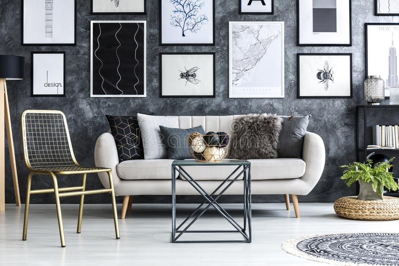Gold chair near beige settee in modern apartment interior with g. Allery of posters royalty free stock photos