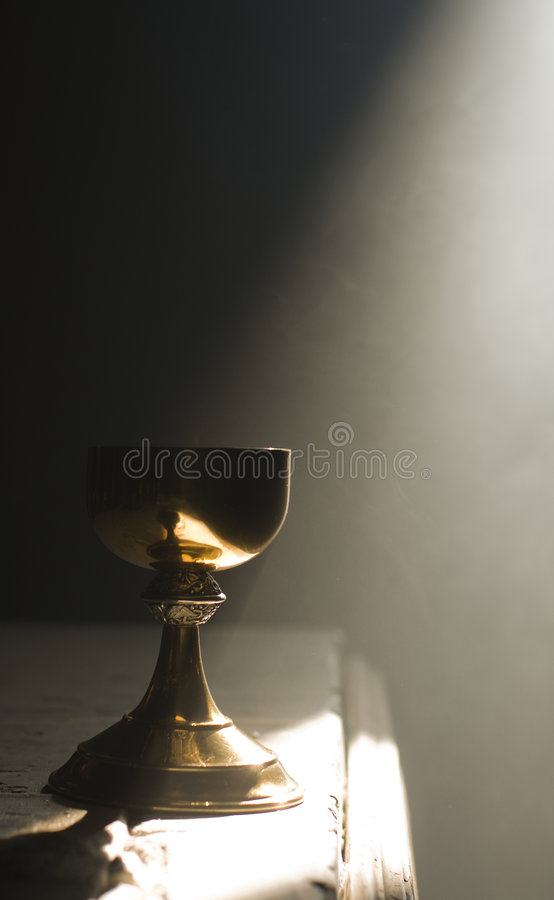 Gold chalice in altar with a ray of divine light stock image