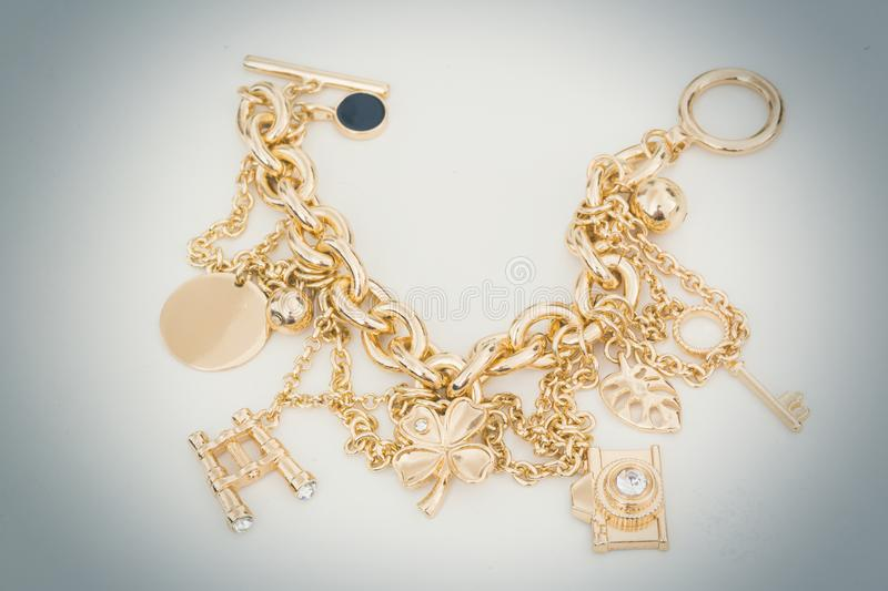 Gold charm bracelet with assorted charms. Laid out on white with a heavy vignette royalty free stock photos