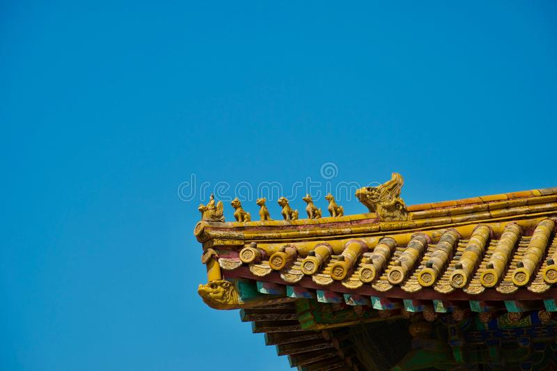 Gold chinese roof with row of mythical animals in sunlight. Gold traditional chinese roof against deep blue summer sky. A row of mythical creatures including a stock photo
