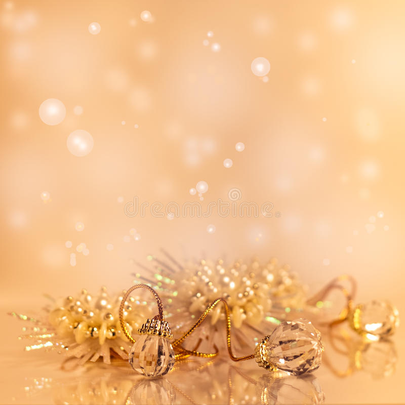 Gold Christmas background. Shiny gold christmas holiday decorations on neutral background with some reflections. Greeting card design stock image