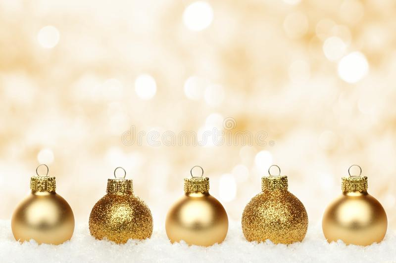 Gold Christmas background with baubles in snow. Christmas background with shiny gold baubles resting in snow and twinkling background stock photography