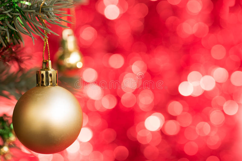 Gold christmas ball ornament decorate on fir tree with red bokeh royalty free stock images