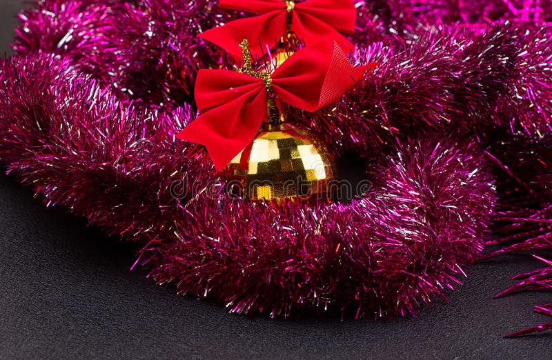 Gold Christmas balls and bright sparkling golden tinsel with red bows royalty free stock photography