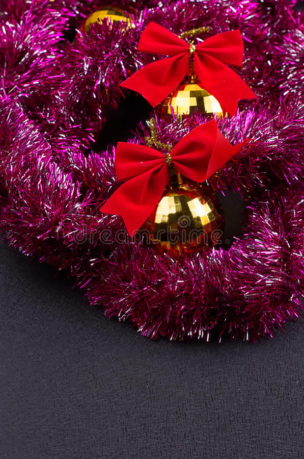 Gold Christmas balls and bright sparkling golden tinsel with red bows stock image