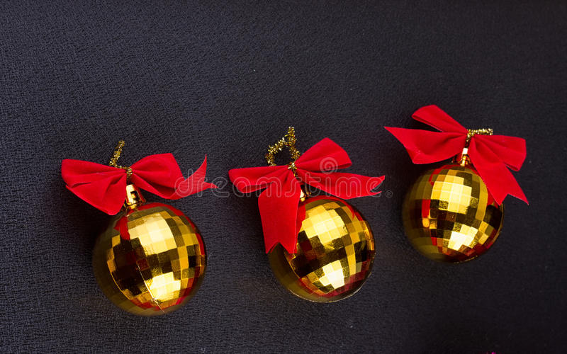 Gold Christmas balls with red ribbons stock photography