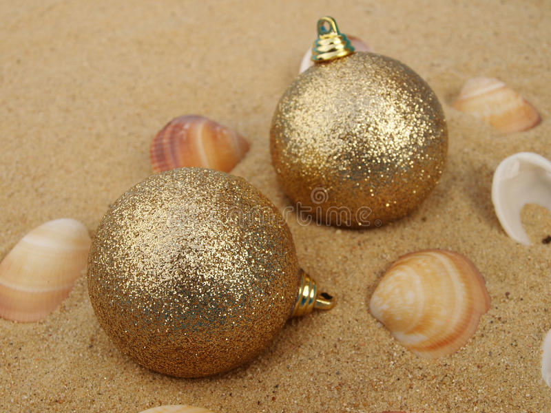 Gold christmas balls in sand stock photo