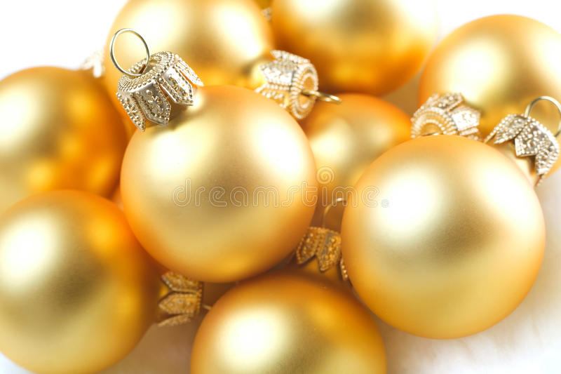 Gold Christmas baubles. Pile of gold colored Christmas baubles or balls stock image