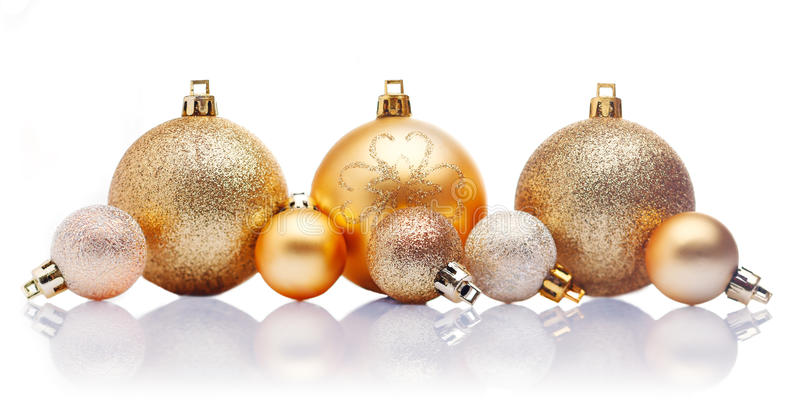 Gold Christmas baubles. A line of large and small gold Christmas baubles with reflections against a white background stock images
