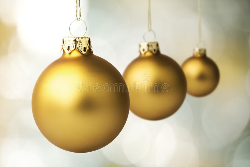 Gold Christmas Baubles. Three gold christmas baubles with strings royalty free stock images