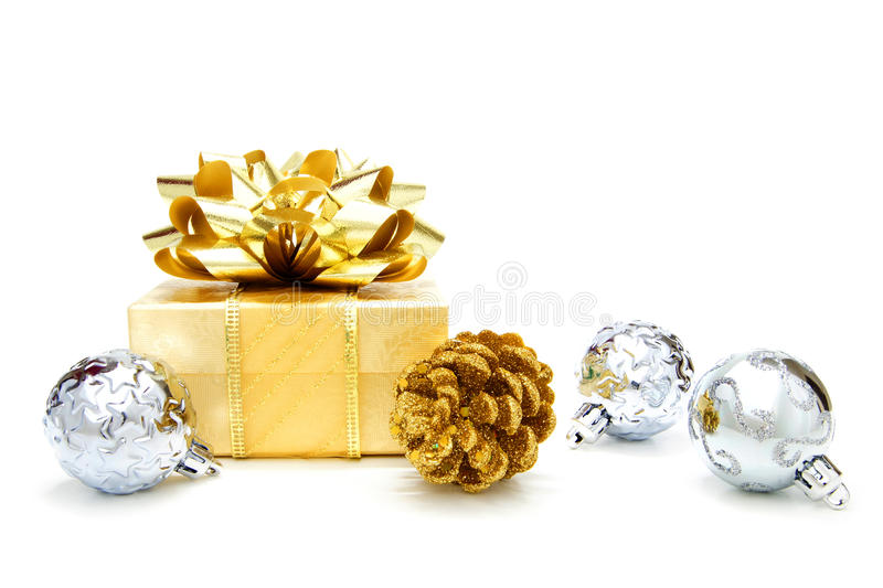 Gold Christmas gift with baubles. Gold Christmas gift box with silver baubles over a white background royalty free stock images