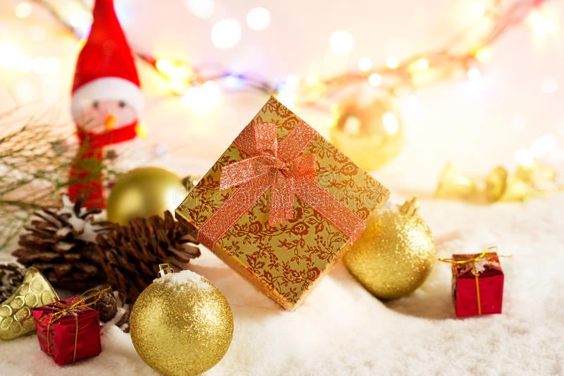 Gold Christmas gift boxes with snowman and bauble on snow in lighting colorful stock photography