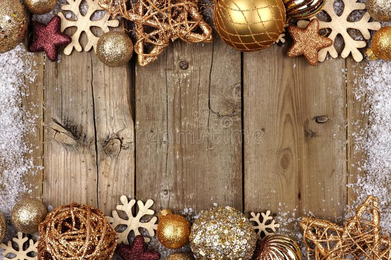 Gold Christmas ornament double border with snow frame on wood. Gold Christmas ornament double border with snow frame on a rustic wood background royalty free stock image