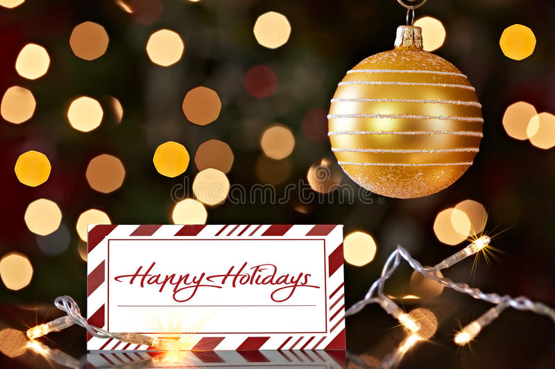 Gold Christmas Ornament And Happy Holiday Card. Gold Christmas Ornament And Colorful Red Striped Happy Holiday Card ~ Christmas Lights Bokeh Background stock images