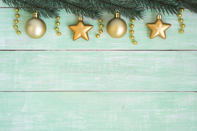 Gold christmas ornaments hanging on fir branch over green vintage backgeound royalty free stock image