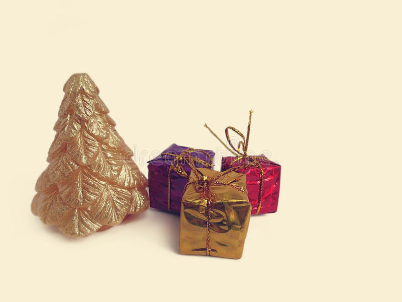 Gold Christmas tree candle and small gifts. On a light background stock image