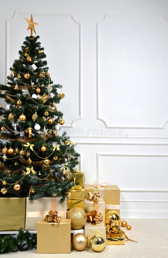 Gold Christmas tree with golder patchwork ornament artificial st. Decorated gold Christmas tree with golder patchwork ornament artificial star hearts presents stock images