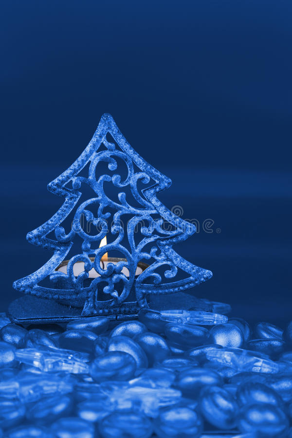 Gold Christmas tree shaped tea light holder. With Yellow clear glass stars and gold pebbles in foreground stock photos