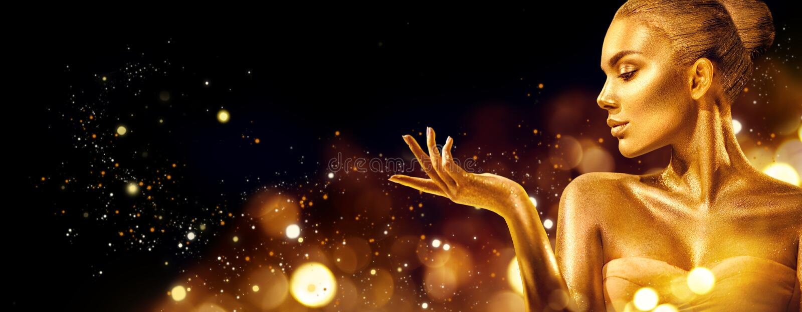 Gold Christmas woman. Beauty fashion model girl with golden makeup, hair and jewellery pointing hand on black royalty free stock photos