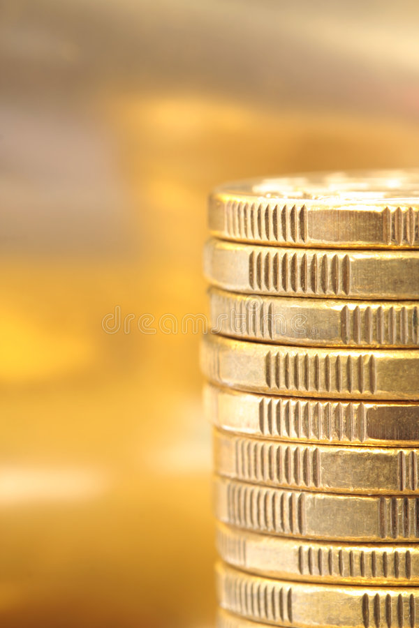 Gold Coins. In a stack, with golden background royalty free stock photography