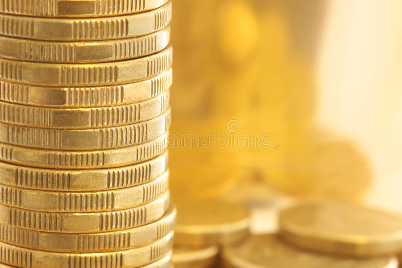 Gold Coins. In closeup, with golden light background stock images