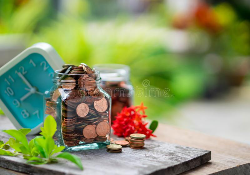Gold coins in glass bottle and clock, time and save money royalty free stock photography