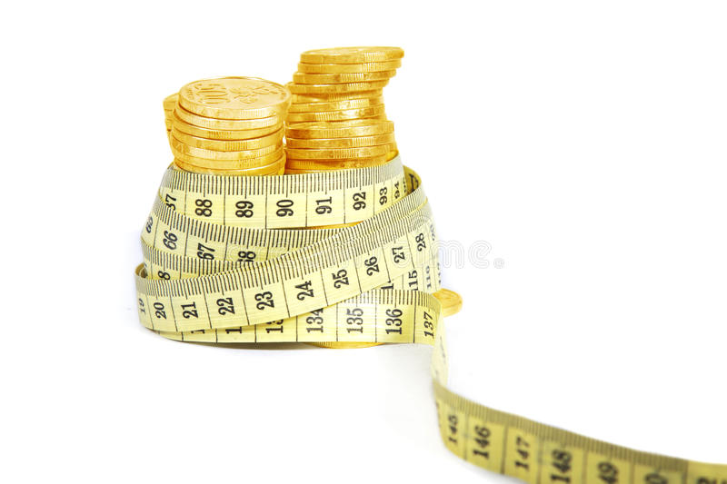 Gold coins with measurement tape royalty free stock image