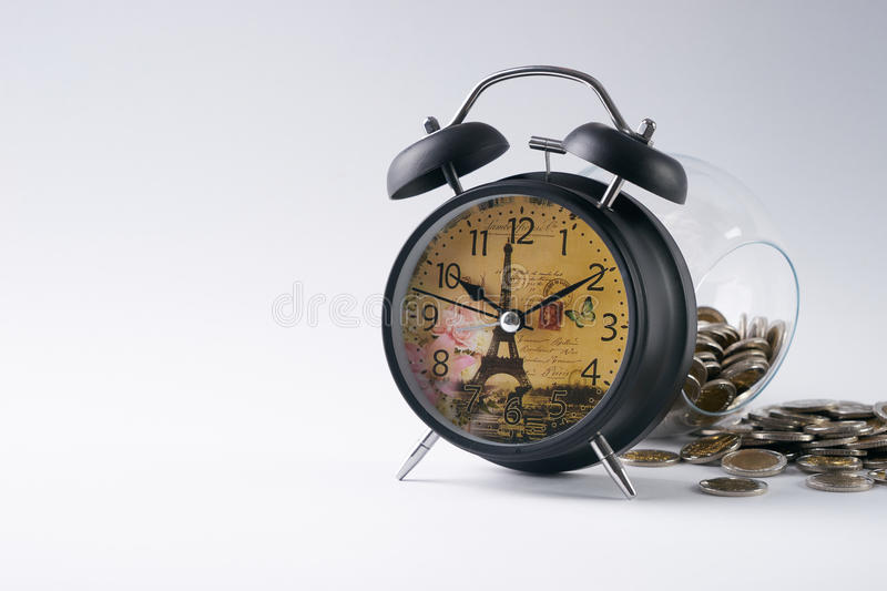 Gold coins, saving money. Gold coins in glass piggy box behind the vintage clock on isolated white background, investment and financial concept.Copy space stock photo