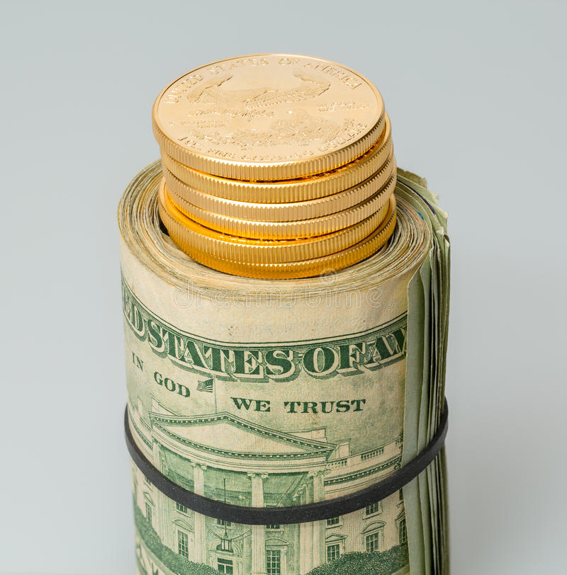 Roll of $20 dollar bills with gold coins royalty free stock image