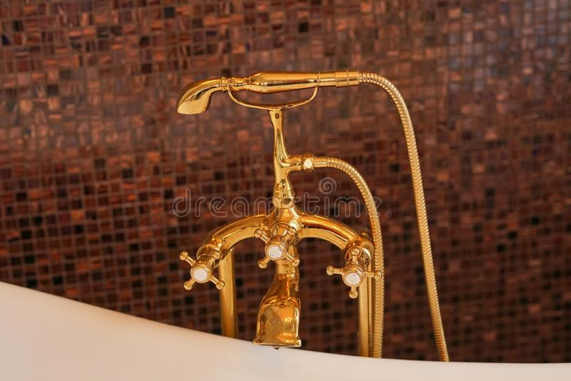Gold color faucet on brown mosaic wall background stock images
