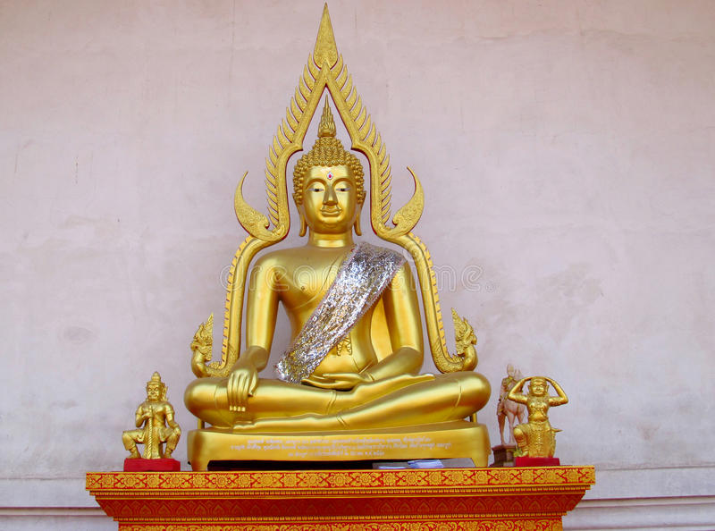 Gold-colored Buddha statue in Buddhist temple. Statue of seated Buddha and colored like gold. Buddha statue in a Buddhist temple. Sacred relic of Buddhism royalty free stock image