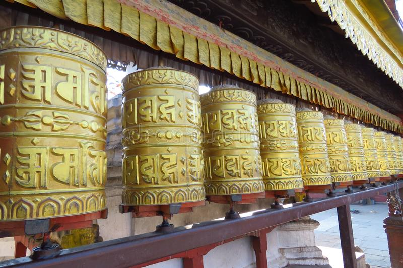 Prayer wheels at Swayambhunath Temple aka Monkey Temple, Kathmandu, Nepal. Gold colored Buddhist prayer wheels at Swayambhunath Temple aka Monkey Temple stock photos