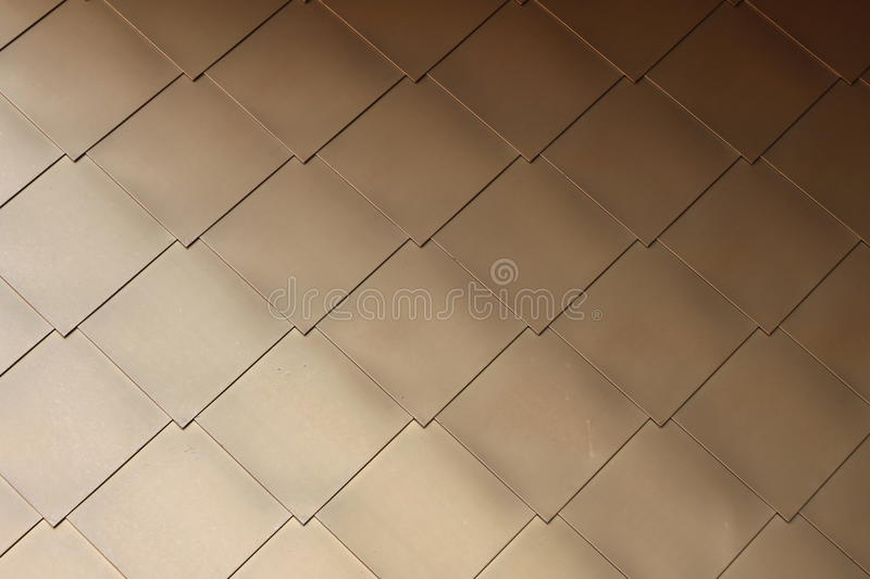 Gold-coloured metal scales on modern building #3. Gold or brass coloured diamond-shaped metal scales on a modern building stock photography