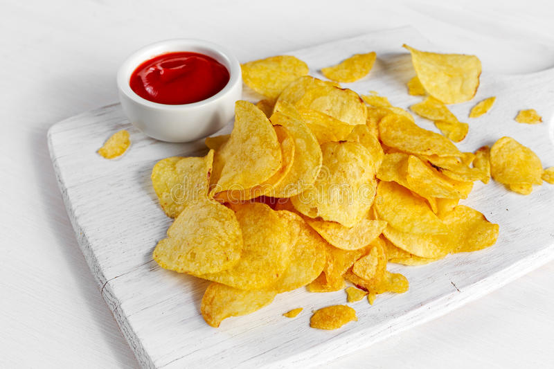Gold and Crispy Potato Chips with hot sauce on white board, background. Gold and Crispy Potato Chips with hot sauce on white board, background royalty free stock images