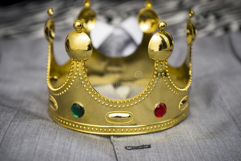 Gold crown lying on the suit of a businessman. Business concept. Metaphor.  royalty free stock image