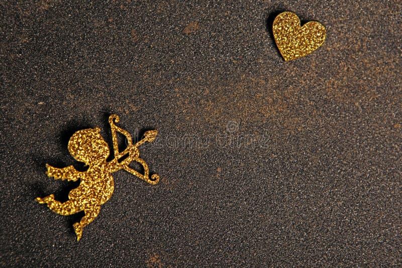 Gold cupid heart asphalt background. Studio stock images