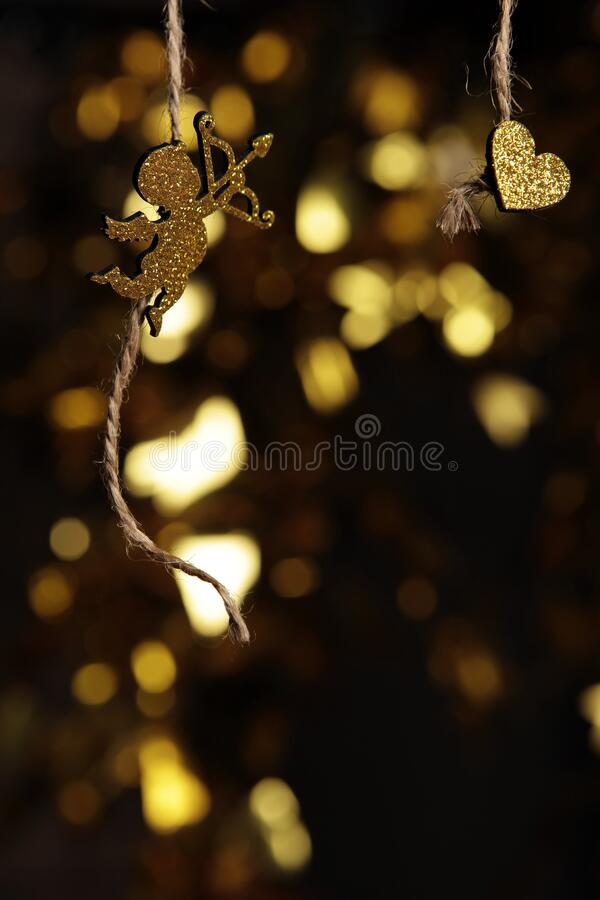 Gold cupid heart rope dark background. Studio royalty free stock photography