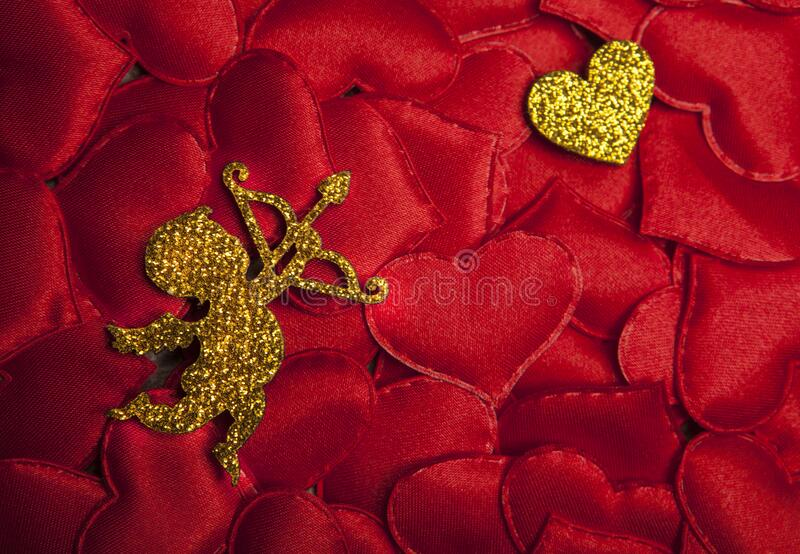 Gold cupid red heart background. Studio royalty free stock image