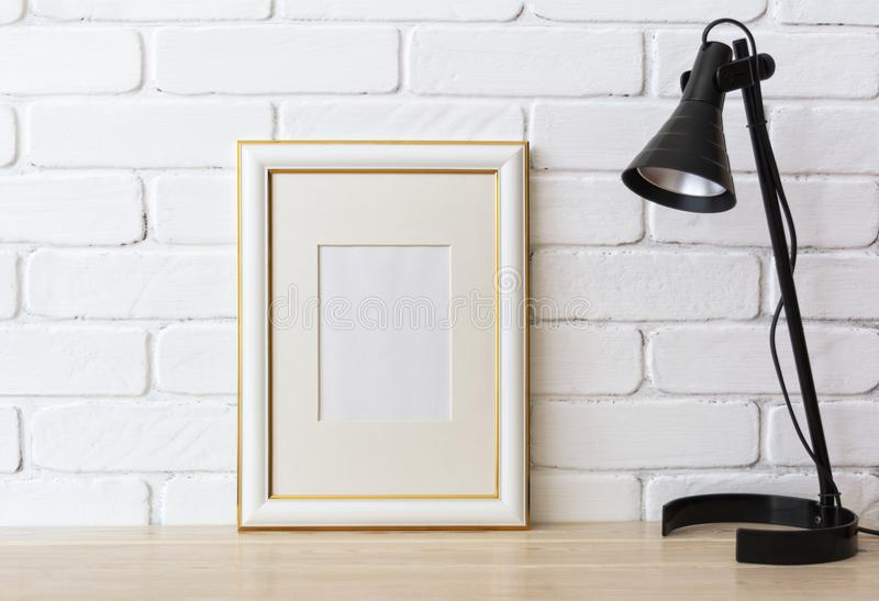 Gold decorated frame mockup with black lamp. Gold decorated frame mockup with black table lamp near painted brick wall. Empty frame mock up for presentation stock image